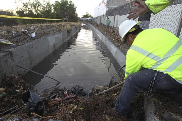 Cal Trans workers clear a clogged storm drain after a deluge of water and mud closed the Golden State Freeway in the Sun Valley section of Los Angeles