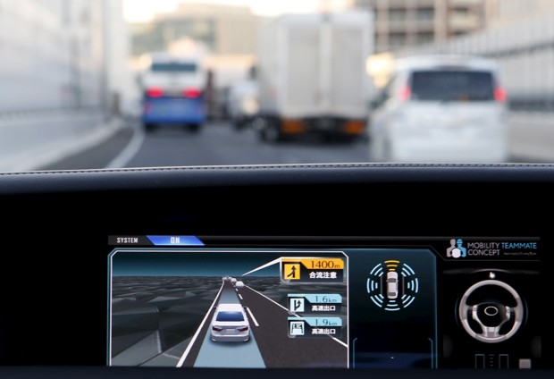 """An onboard display monitor shows other vehicles as a staff member of Toyota Motor Corp drives its self-driving technology """"Mobility Teammate Concept"""" prototype car hands-free on the Metropolitan Expressway in Tokyo"""